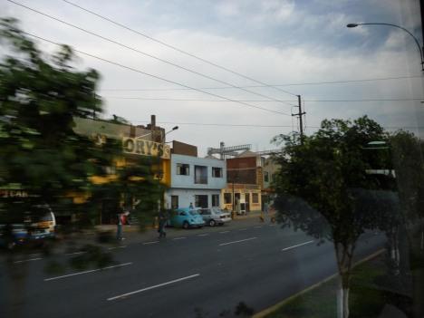 Et av de mange fargerike husene langs veien til hotellet. I midtdrabanten er det frodige, grønne trær, og folk sitter og spiller kort eller tar en lur mellom bilene som dundrer forbi.
